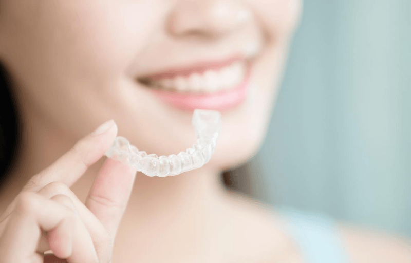 woman holding invisible aligner