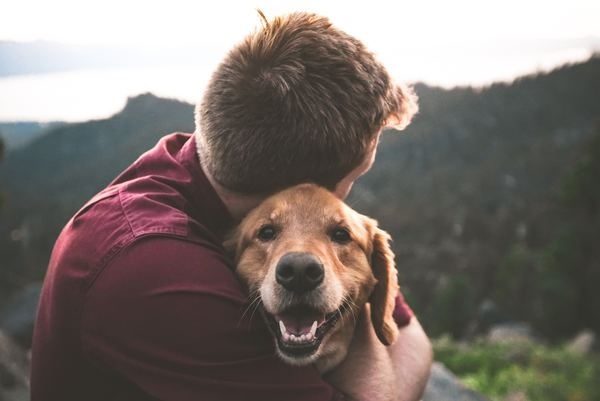 Man hugging happy dog