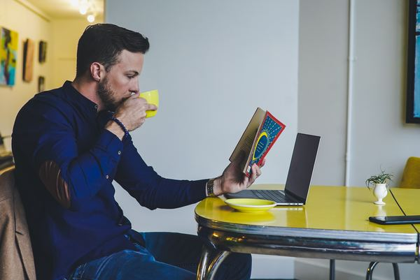 man drinking coffee at a table while reading a book